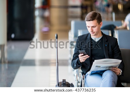 Passenger in an airport lounge waiting for flight aircraft. Young man with cellphone in airport waiting for landing