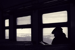 Passenger in train reading book. Journey by rail. Read on road. Winter landscape in window. Loneliness and solitude. Toned black and white color processing. Nice soft warm light