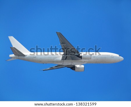 Passenger jet airliner / airplane in flight, clear blue sky (sky is the original natural background). Side view. - stock photo