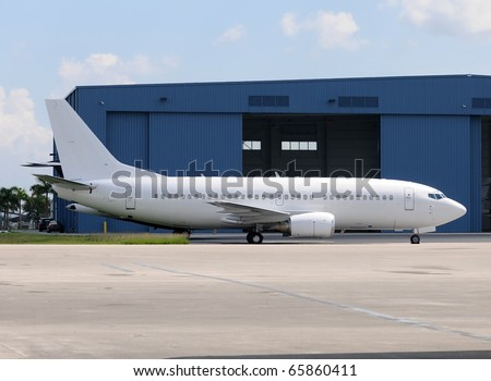 Passenger jet airplane in unmarked white color
