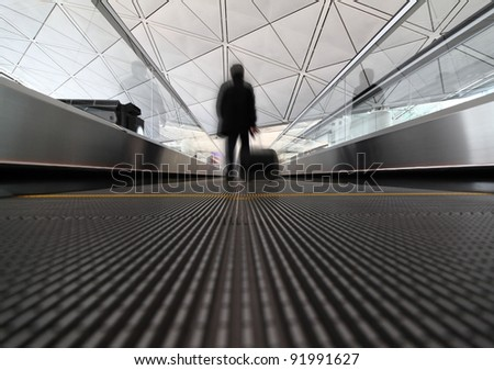 passenger (Man) rushing through an escalator in airport terminal