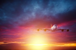 Passenger plane, airliner flies against the backdrop of a beautiful sunset. Travel concept, air travel. Copy space
