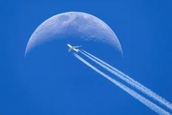 Passenger plane - airliner passes near the moon. Explore new frontier. Space traveler concept