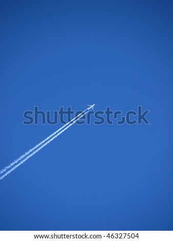 passenger plane flies across a blue sky leaving vapour trails