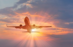 passenger plane fly down over take-off at sunset