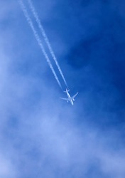 Passenger plane in flight, at high altitude, among the clouds. Contrail.
