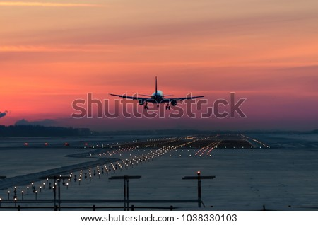 passenger plane is landing in the airport runway at early morning at sunrise time in the frosty winter air