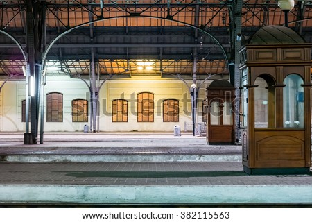 Passenger platform at night on the railway station. Train station at night.