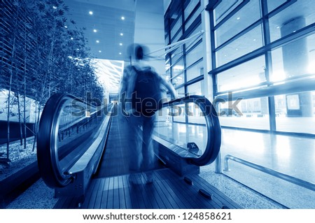passenger rushing through an escalator in airport terminal - stock photo