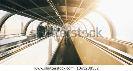 passenger rushing through an escalator in airport terminal  #1363288352