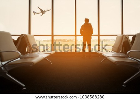 Passenger seat in departure lounge for see airplane, View from airport terminal. Sun light in vintage color selective focus, Transport and travel concept