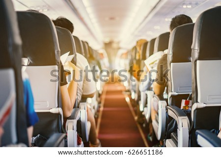 passenger seat, Interior of airplane with passengers sitting on seats and stewardess walking the aisle in background. Travel concept,vintage color,selective focus #626651186