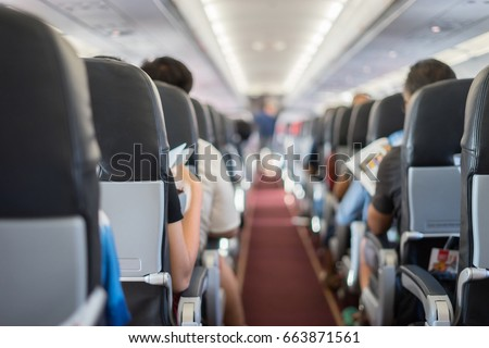 passenger seat, Interior of airplane with passengers sitting on seats and stewardess walking the aisle in background. Travel concept,vintage color - Shutterstock ID 663871561
