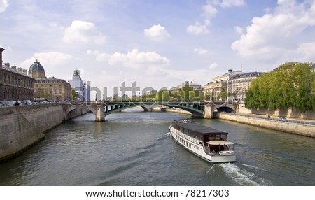Passenger ship boat sails on the river Seine. View from the Quay. Urban scene. Paris