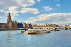 Passenger ships and service boats in front of Parliament of London, UK, on a bright day