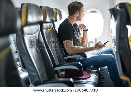 Passenger sits in the airplane next to the window and holds a cellphone in the hands. He wears a black T-shirt with blue jeans. There is a crimson hat on a seat near him. Horizontal.