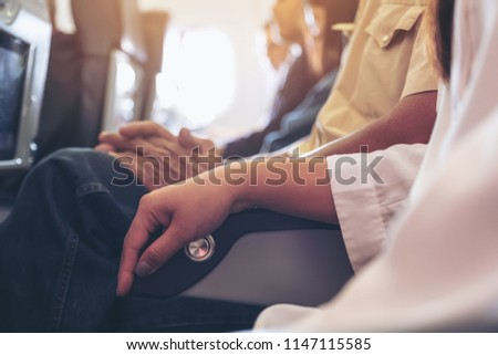 Passenger sitting on a seat row in cabin