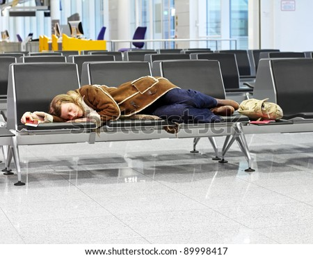 Passenger spending a night at airport after flight cancelation - stock photo