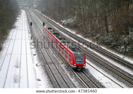 Passenger train at speed on rails by a winter morning
