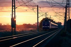 Passenger train of public transport on railroad track at beautiful sunrise.