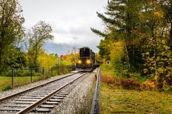 Passenger Train Pulled by a Black Diesel Locomotive on a Cloudy Autumn Day