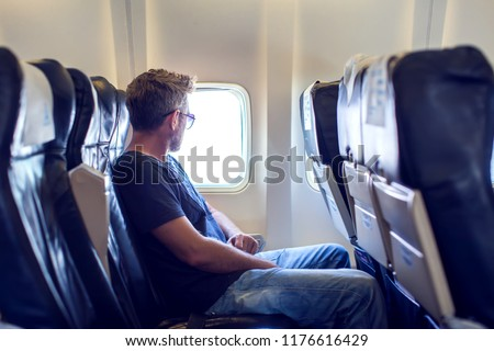 Passenger traveler looking at window in airplane, travel by flight, man tourist sitting in air plane. Travel concept