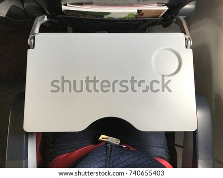Passenger who wears blue jeans is fastening  red seat belt in airplane cabin. There are tray table and seat belt for passenger in each chair on the plane. - Shutterstock ID 740655403