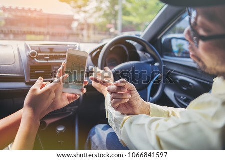 Passengers are instructing using a GPS on a mobile phone with a taxi driver.
