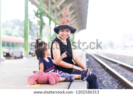 Passengers are waiting for the train She did not celebrate Halloween at home because she was traveling, wears a witch hat to wear to tease her daughter. Emotional of Tourist with Transportation. #1202586313
