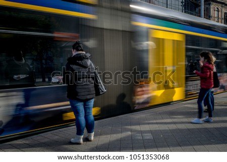 Passengers at the tram stop. Passengers are waiting to take off to the tram that arrives at the stop, blurred tram in the background.