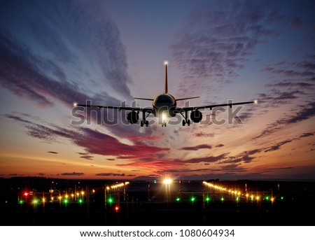 Passengers commercial airplane landing on runway with dramatic sunset sky. Concept of fast travel