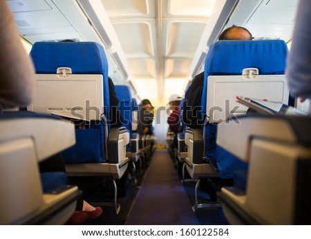 Passengers inside the cabin of a commercial airliner during flight