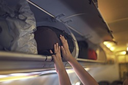 Passengers putting luggage into overhead locker on airplane. Hand putting luggage into panel overhead locker in airplane.
