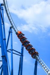 passengers restrained in seats of steel roller coaster trains climbing to a high position in white rail tracks with blue steel supporting posts against blue sky
