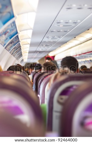 Passengers sitting on their chairs in airplane cabin