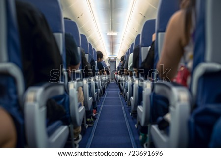 Passengers traveling by a modern commercial plane, shot from the inside of an airplane