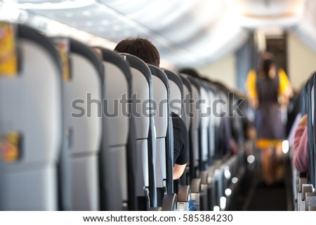 Passengers traveling by a plane, shot from the inside of an airplane #585384230