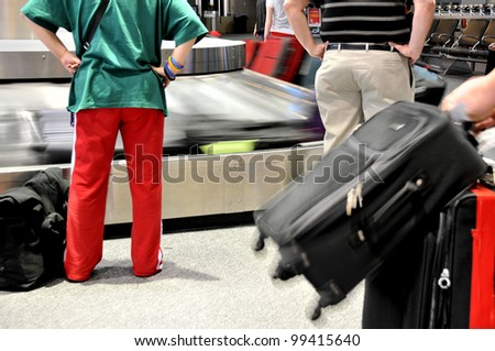 Passengers wait for baggage at airport carousel