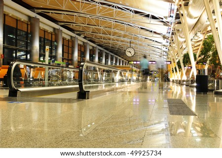 Passengers walking in an airport terminal - slow shutter blur, wide angle.