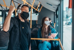 Passengers wearing protective mask while riding a bus and keeping the distance due to a corona virus pandemic