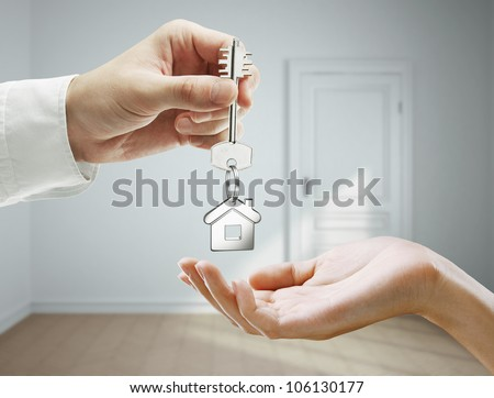 passing keys against backdrop of gray room