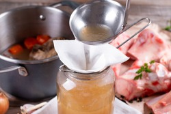 Passing the bone broth through a sieve and through a paper napkin. Concentrated Bone Broth in a Glass Jar
