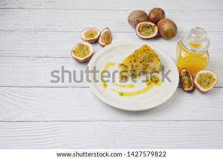 Passion fruit cake placed on a ceramic plate  Decorated with fresh passion fruit  With passion fruit sauce in a glass bottle