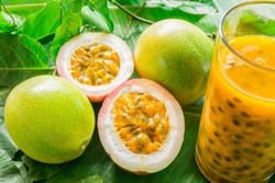 Passion fruits half and juice in a glass jar with leaves on a green background. Healthy fruit concept. Closeup, Select focus.