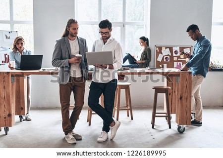 Passionate about their project. Full length of young modern people in smart casual wear smiling and discussing something while working in the creative office  #1226189995