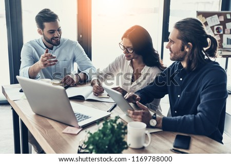 Passionate about their project. Group of young modern people in smart casual wear working together and smiling while sitting in the creative office