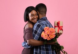 Passionate African American lovers with gift box and beautiful roses hugging on pink studio background. Affectionate black couple celebrating Valentine's Day or anniversary together