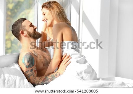 Passionate beautiful couple in bedroom enjoying foreplay #541208005