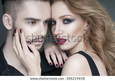 Passionate couple. Beautiful young man and blond woman closeup. Woman hugging man. Love. Flirt. Kiss. Lovers.