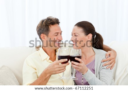 Passionate couple drinking red wine while relaxing on the sofa